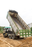 Dump truck dumps its load of rock and soil on land Stock Images