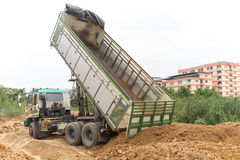 Dump truck dumps its load of rock and soil on land Royalty Free Stock Photo