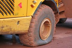 Dump truck with a flat tyre. On a construction site stock image