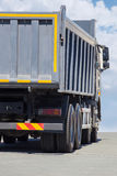 Dump truck goes  on highway Stock Photo