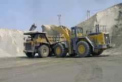 Dump truck and loader. Loading sand with a Komatsu loader into a Cat 85 ton hauler at a stone quarry Royalty Free Stock Photography