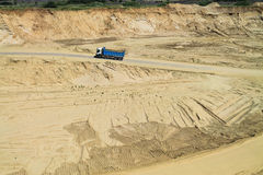 The dump truck moves on a sandpit bottom Royalty Free Stock Photography