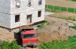 The dump truck near the house under construction, the truck and building of the house from a white brick, the dump truck brought s stock photos