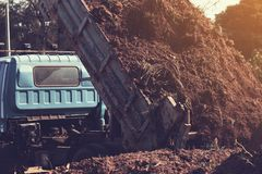 Dump truck preparing ground for landscape improvement at propert. Y project;Dump truck dumping and tipping raw earth soil for construction site royalty free stock images