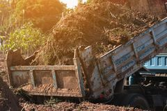Dump truck preparing ground for landscape improvement at propert. Y project;Dump truck dumping and tipping raw earth soil for construction site royalty free stock photos