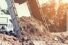 Dump truck preparing ground for landscape improvement at propert. Y project;Dump truck dumping and tipping raw earth soil for construction site royalty free stock photography