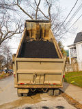 Dump Truck in residential street. Dump truck with load of asphalt ready to resurface road royalty free stock photo