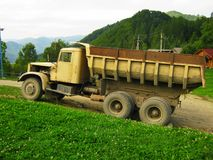 Old dump truck on the road high in the mountains stock image