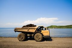Dump truck & sea. Dump truck on a background of the sea royalty free stock photography