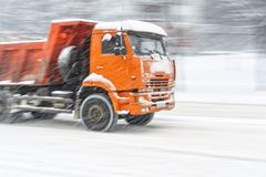 Dump truck in snow storm. Big orange dump truck rides on a snowy road during a snow storm. Blurred in motion background royalty free stock images