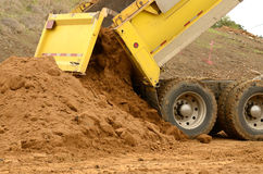 Dump Truck. Ten yard dump truck delivering a load of dirt for a fill project at a new commercial development construction project Stock Images