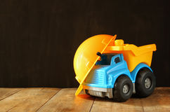Dump truck toy and safety hat over wooden textured background Royalty Free Stock Images