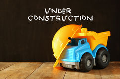 Dump truck toy and safety hat over wooden textured background Stock Image