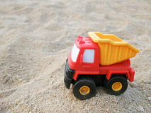 Dump truck toy. Working on the sand.children's toys Royalty Free Stock Photo