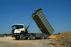 Dump truck unloading soil. On construction site to building road Royalty Free Stock Photography