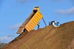 Dump truck unloading soil during road works stock photos