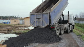 Dump Truck unloads the ground at the construction site. Building materials stock footage