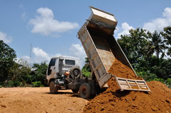Dump truck at work. White dump truck dumping soil in my home ground Royalty Free Stock Photo