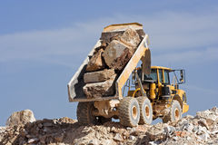 Dump truck at work. Heavy dump truck against blue sky operating in a marble quarry Stock Images