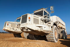 Dump Trucks. A couple of dump truck on dirt against a deep blue sky royalty free stock image