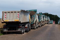 Dump Trucks. Row of Dump Trucks and Earth Moving Equipment at a Highway Construction Site in Germany stock photography
