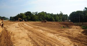 Dump trucks and bulldozers clear land for a new roadway Royalty Free Stock Photo