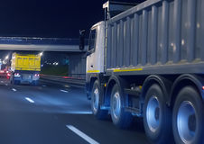 Dump trucks transport freight on the night. Highway Stock Photography