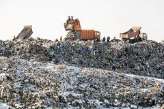 Dump trucks unloading waste over huge sanitary fill. Environmental pollution. Out of date technology.  royalty free stock photography