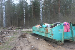 The dump in the woods. Environmental pollution. Rubbish in the forest. Waste mixed. Contaminated nature Stock Photos