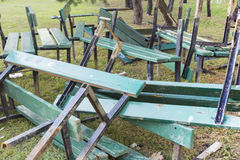 Dumped in a pile of broken wooden green benches . Reconstruction and repair in city Park royalty free stock image