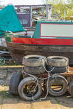 Dumped tyres. Vehicle tyres dumped in a boatyard alongside an abandone narrowboat Royalty Free Stock Photos