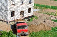 Dumper nära huset under konstruktion, lastbilen och byggnad av huset från en vit tegelsten, dumper kom med s arkivfoton