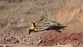 A dumper rides along the road in a quarry, a yellow mining dump truck, a panorama. The dump truck is in the quarry. Dump truck is in the quarry in good weather stock footage
