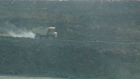 Dumper in a stone quarry. A large dump truck is moving along a stone quarry stock video footage
