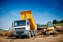 Dumper truck and bulldozer at road construction site Stock Image