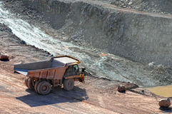 Dumper truck driving around in open pit mine of porphyry rock. Royalty Free Stock Photography