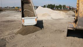 Dumper truck is unload soil. Dumper truck is unloading sand in excavator range at construction site stock video