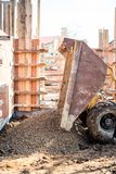 Dumper truck unloading construction gravel, granite and crushed stones at building foundation Stock Photos