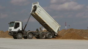 Dumper truck unloading soil at construction site during road works.  stock video footage