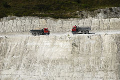 Dumper trucks in a chalk pit. Going dumper trucks in after the hillside in a chalk pit Royalty Free Stock Photos