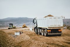 Industrial dumper trucks working on highway construction site, loading and unloading earth. heavy duty machinery activity Stock Photos