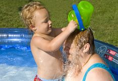 Dumping a Bucket. Young boy dumping a bucket of water on a woman in swimming pool Royalty Free Stock Photos