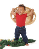 Dumping Christmas. An adorable toddler laughing at the mess he created when he dumped Christmas ornamants from the wicker basket he holds.  On a white background Royalty Free Stock Images