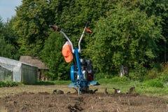 Dumping de la terre dans le jardin avec un cultivateur image libre de droits