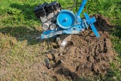 Dumping della terra nel giardino con un coltivatore Fotografie Stock Libere da Diritti