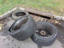 Dumping illégal, pneus près d'un égout de tempête Photos libres de droits