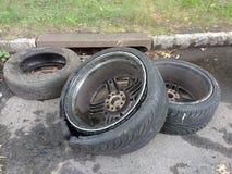 Dumping illégal, pneus près d'un égout de tempête Photos stock