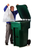 Dumping Trash. A mature man dumping the household trash in a green dumpster. Isolated on white stock image