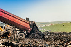 Dumping truck getting trash moved on construction site. Dumping site Stock Photo