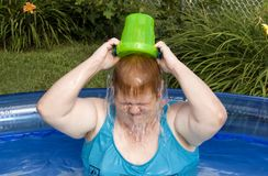 Dumping Water. Woman playing in pool by dumping bucket on head Stock Photo
